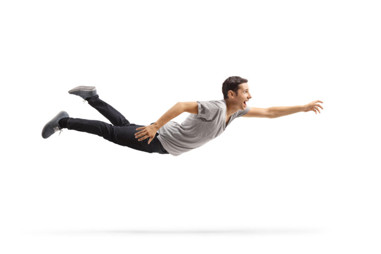 Casual young man flying and reaching for something